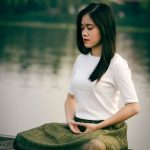 Woman meditating in a lotus position near a river